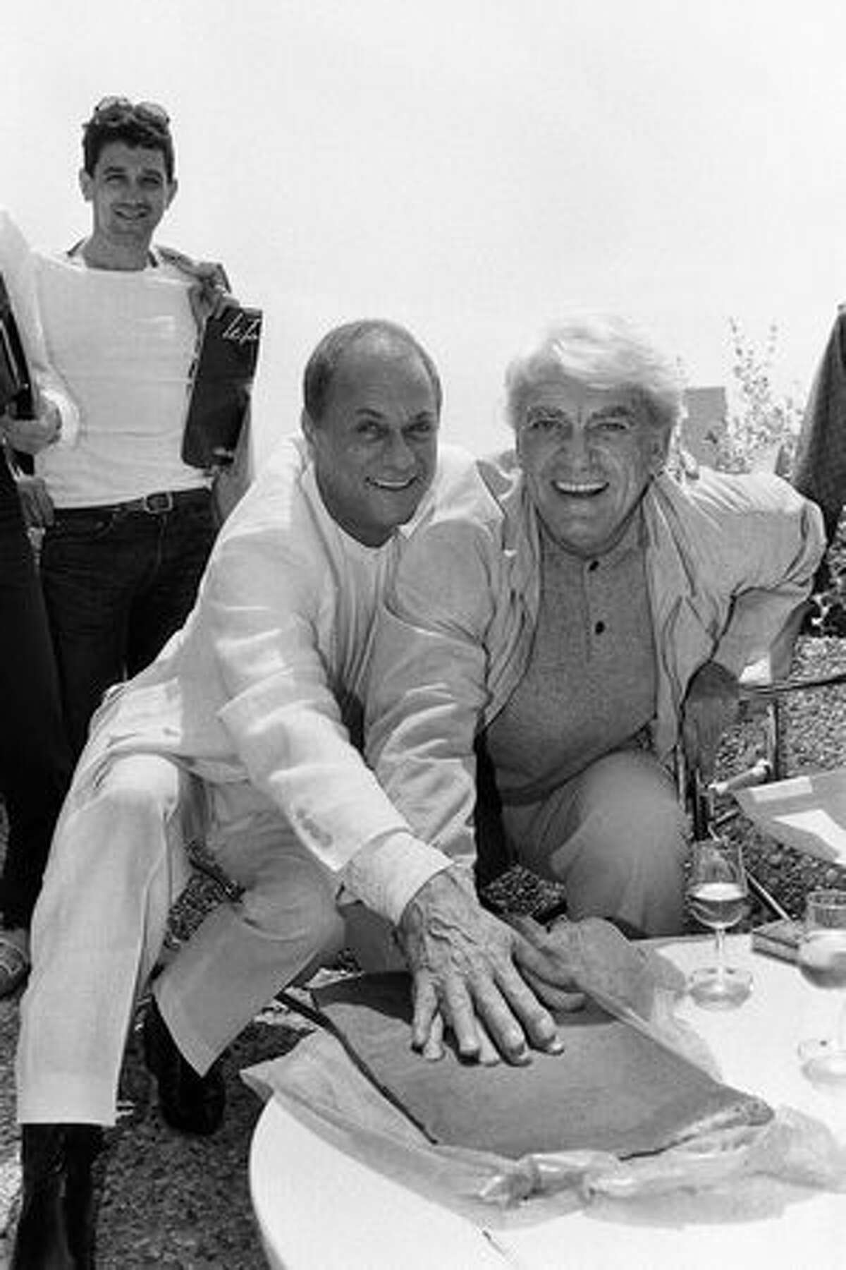 American actor Tony Curtis is pictured hand on hand with French actor Jean Marais May 22, 1984, in Cannes during the 37th International Film Festival. (FILM) AFP PHOTO/RALPH GATTI