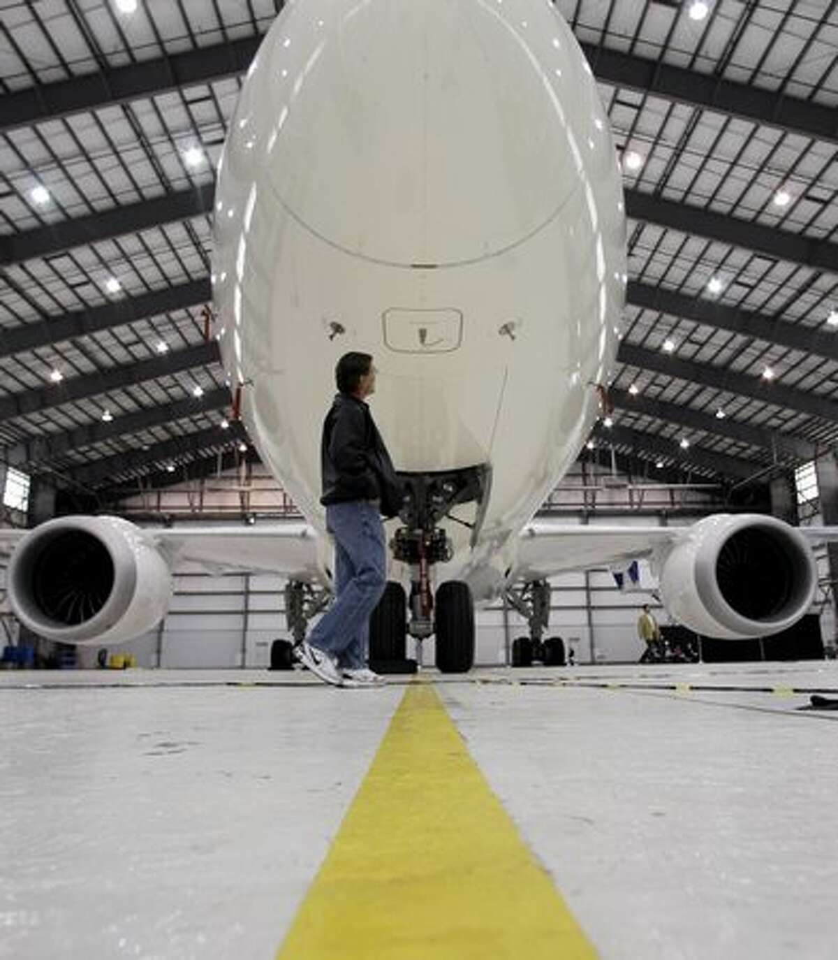 A worker looks at a Japan Airlines Boeing 787 on Friday, March 11, 2011, at Boeing's Global Services & Support site in San Antonio. Boeing held an arrival ceremony for the aircraft, which will get its final upgrades in San Antonio. (AP Photo/Eric Gay) Related story