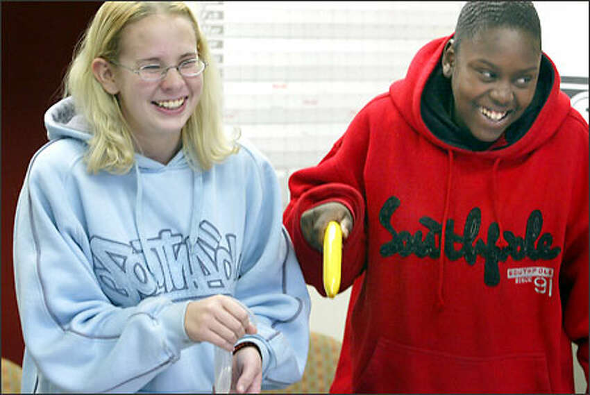 Lindsey Northover, 15, left, of Kirkland and Cyntillia Sullivan, 17, of Seattle can/t help but giggle as they present the facts about condom use.