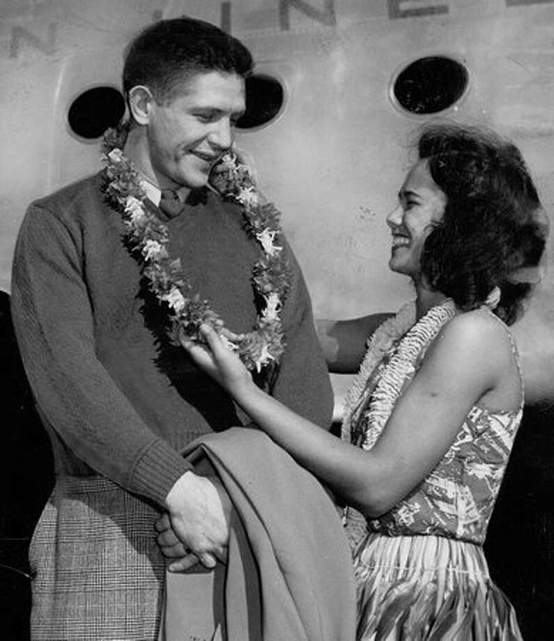 "The December 1946 photo caption read: Marv Harshman, one of the two ""Marvelous Marvs"" of the Tacoma Indians' pro football team, is presented with a lei and aloha greeting by Mildred Irving upon the team's arrival at Honolulu for a game against the Warriors. Photo: P-I File"