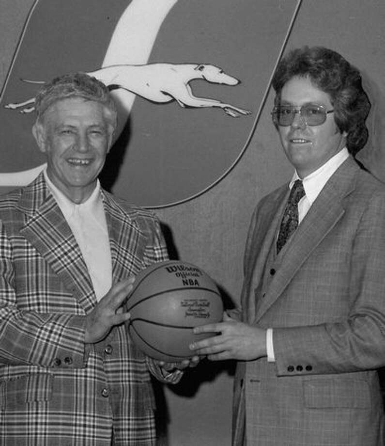 UW basketball coach Marv Harshman is pictured here with Gran Griffin, promotion director of Northgate Center, Inc. Harshman sent the basketball to a seven-year-old disabled boy in Bellingham. Dec. 10, 1975. Photo: P-I File