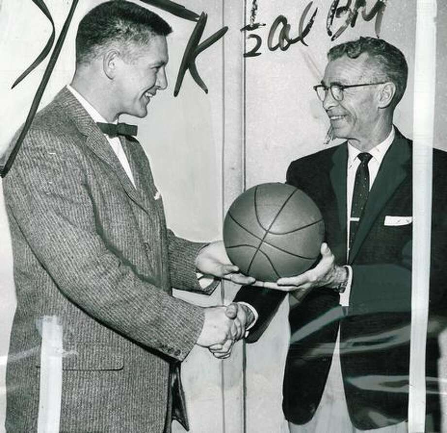 Jack Friel, right, retired as the Washigton State University basketball coach in 1958. Friel is shown here turning the basketball over to the new Cougar coach, Marv Harshman at a meeting of the Puget Sound Sportswriters and Casters organization. Photo: P-I File