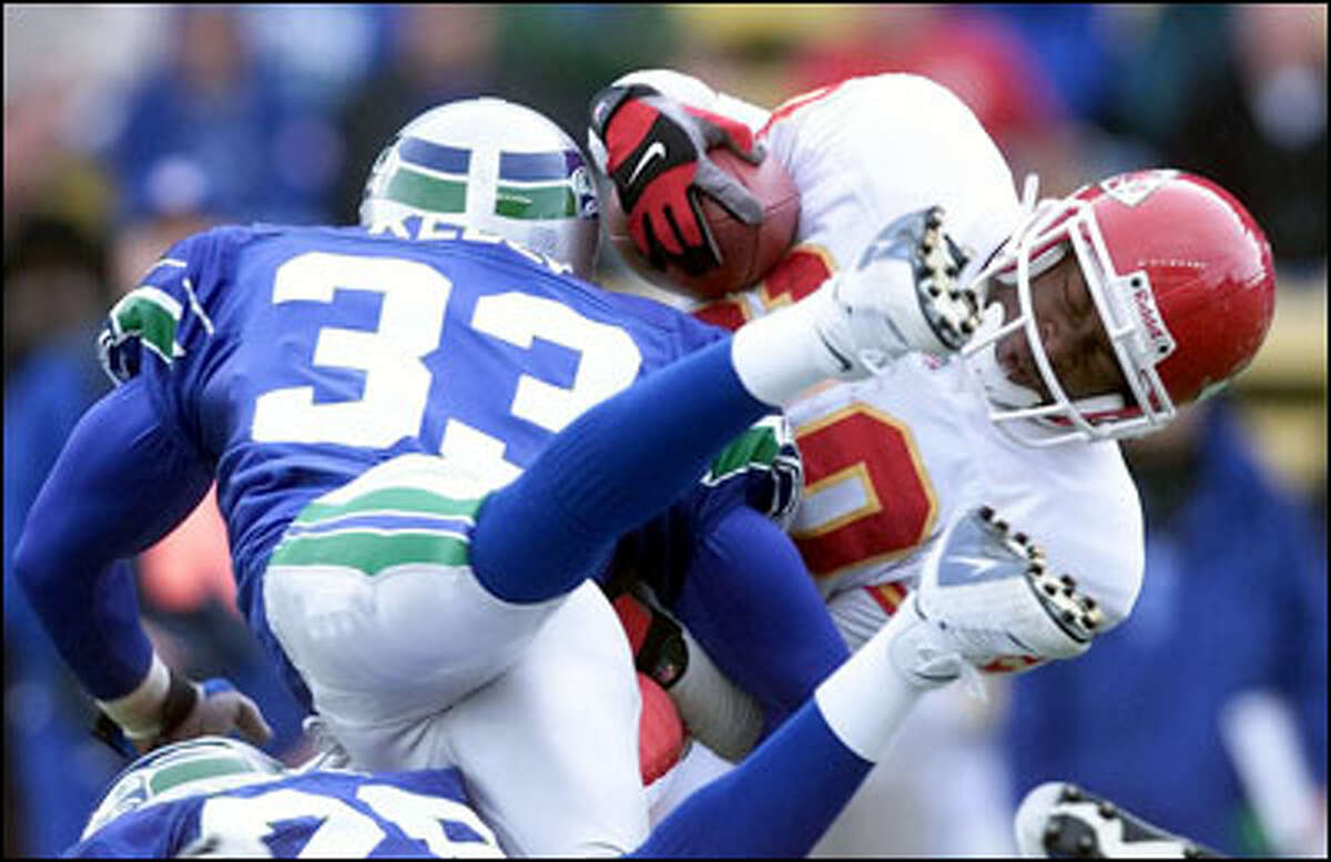 Dante Hall runs back 16 yards on a kickoff return as Maurice Kelly stops him in the second quarter.