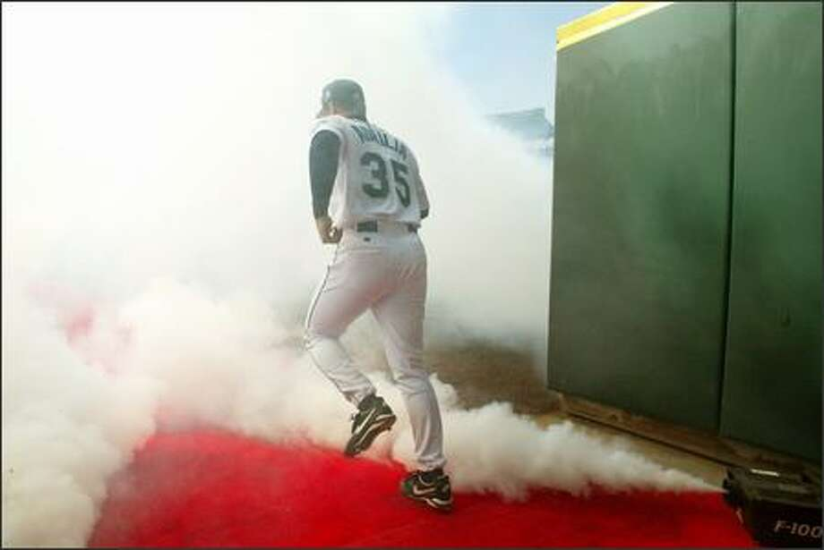 New Mariners shortstop Rich Aurilia runs through the theatrical smoke during Opening Day introduction ceremonies. Photo: Mike Urban, Seattle Post-Intelligencer