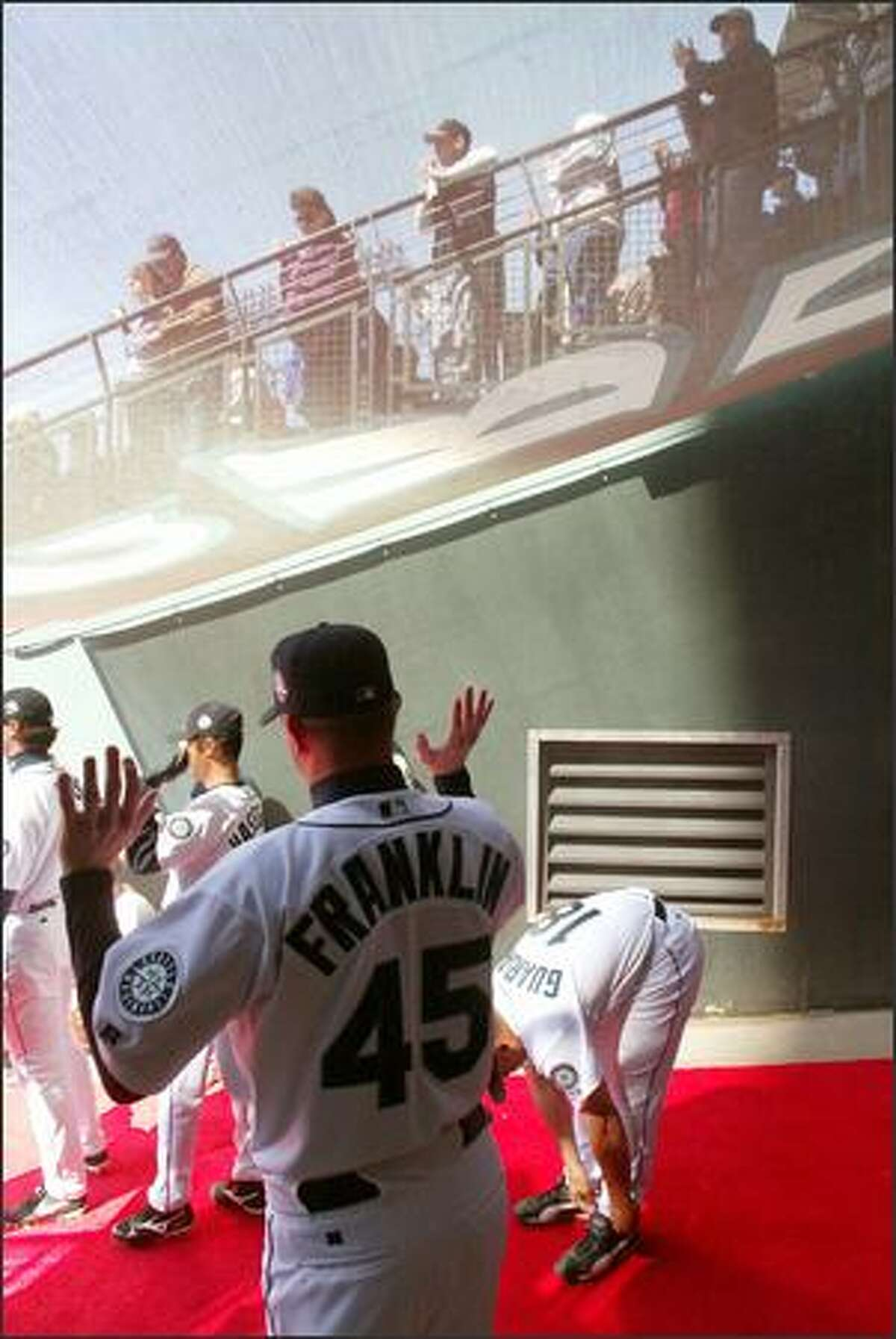 Mariners pitcher Ryan Franklin motions for fans to pump up the volume while waiting backstage to be introduced.