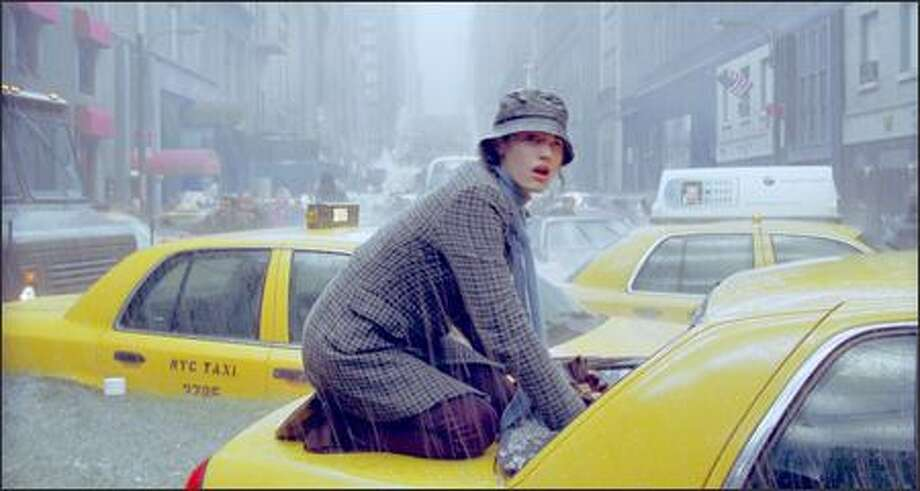 Seconds before Fifth Avenue is buried underwater, Emmy Rossum comes to the aid of a trapped taxi passenger. Photo: Twentieth Century Fox