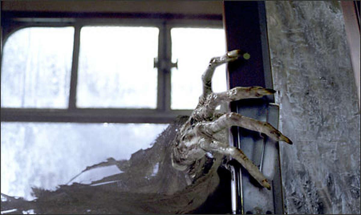 A Dementor's claw reaches through the window.