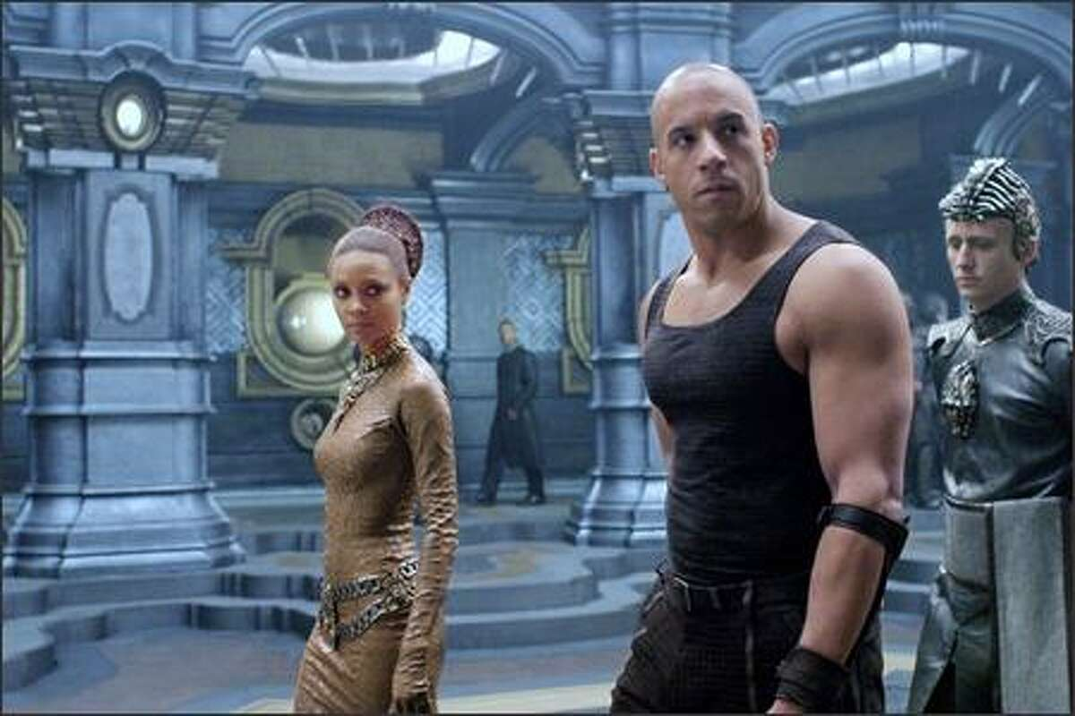 Dame Vaako (Thandie Newton), Riddick (Vin Diesel) and The Purifier (Linus Roache) aboard the Necromonger command ship.