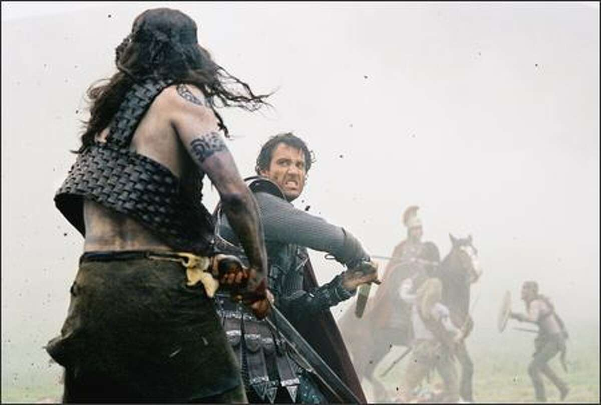 Arthur (Clive Owen) comes to the aid of Romans under attack by Picts, or Woads.