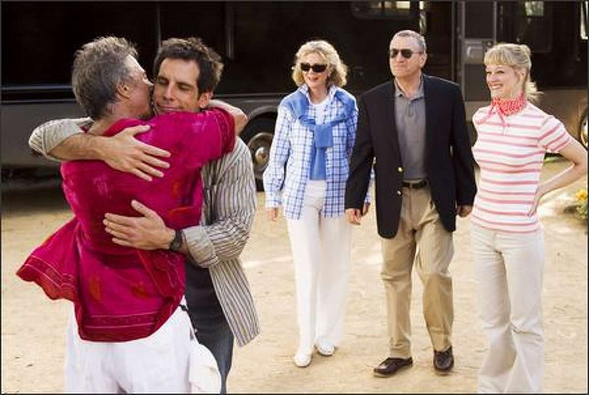 Greg Focker (Ben Stiller) hugs his dad Bernie (Dustin Hoffma) while his soon-to-be inlaws stand in the background.