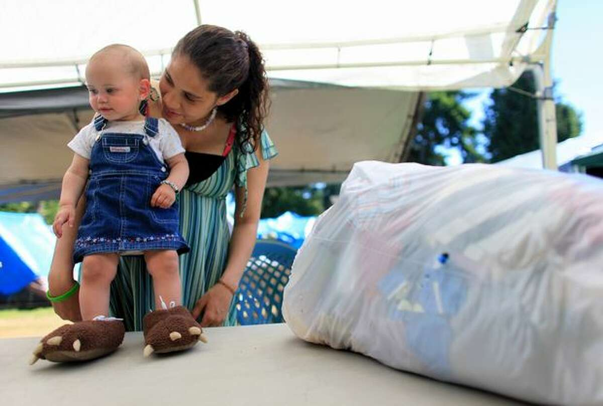 Casi Jackson and her daughter Tiana prepare to go through a bag of donated clothing to see if anything fits Tiana at Tent City, a temporary camp for homeless people, at Lake Washington United Methodist Church in Kirkland on July 6, 2010. Casi visited the camp as part of an outreach program. She was homeless and now lives in a subsidized apartment.