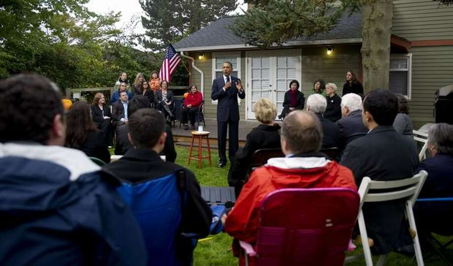 President Barack Obama talks in the backyard of the home of Erik and Cynnie Foss, in Seattle. Photo: Getty Images