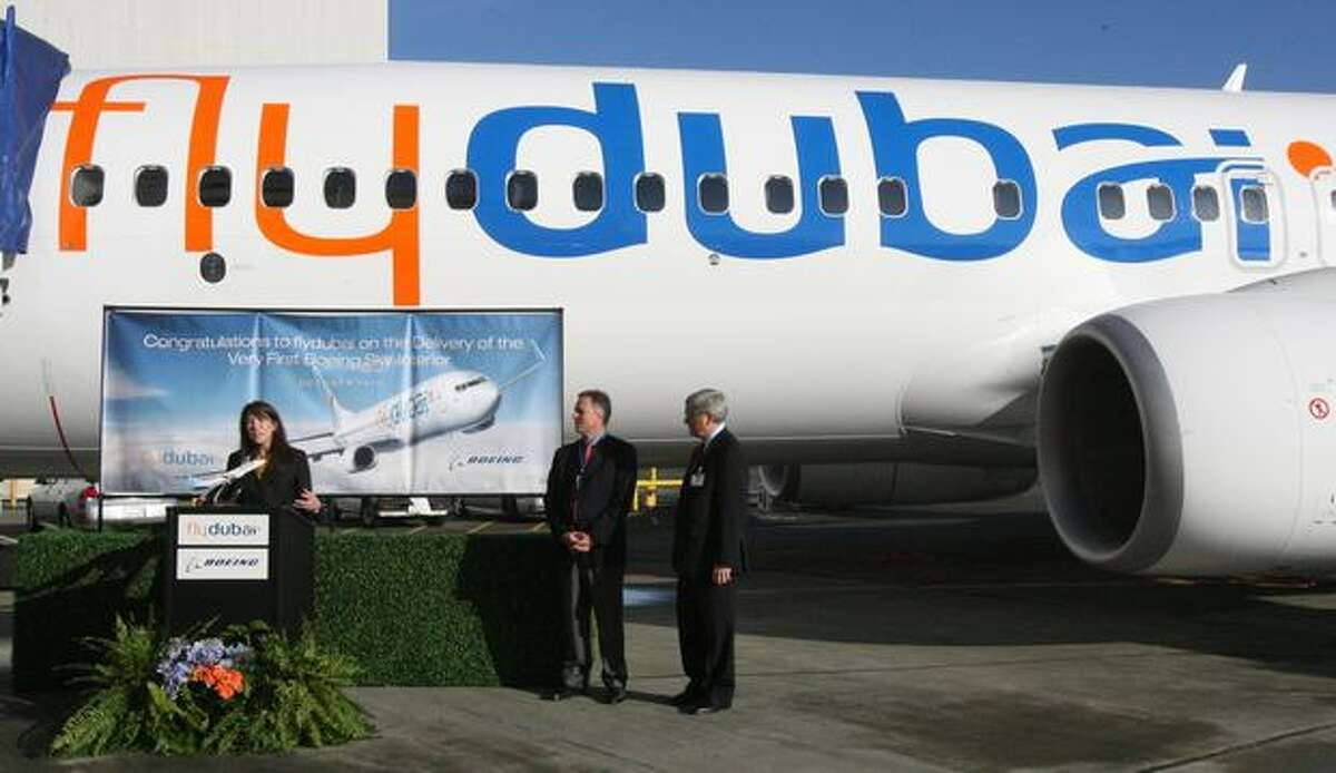 Beverly Wyse, vice president and general manager of Boeing's 737 Program, speaks during a delivery ceremony at Seattle's Boeing Field for flydubai's new Boeing 737-800, the first with a Boeing Sky Interior, while flydubai Chief Operating Officer Kenneth Gile (right) and Ken Schulz, Boeing's Dubai-based sales director, listen. sits at Boeing Field, in Seattle, before its delivery ceremony.