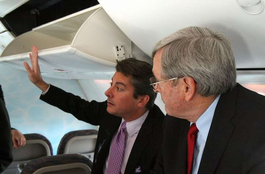 Kent Craver, regional director of passenger satisfaction and revenue at Boeing Commercial Airplanes, demonstrates the larger overhead bins on the Sky Interior 737 as flydubai Chief Operating Officer Kenneth Gile looks on. Photo: Aubrey Cohen, Seattlepi.com
