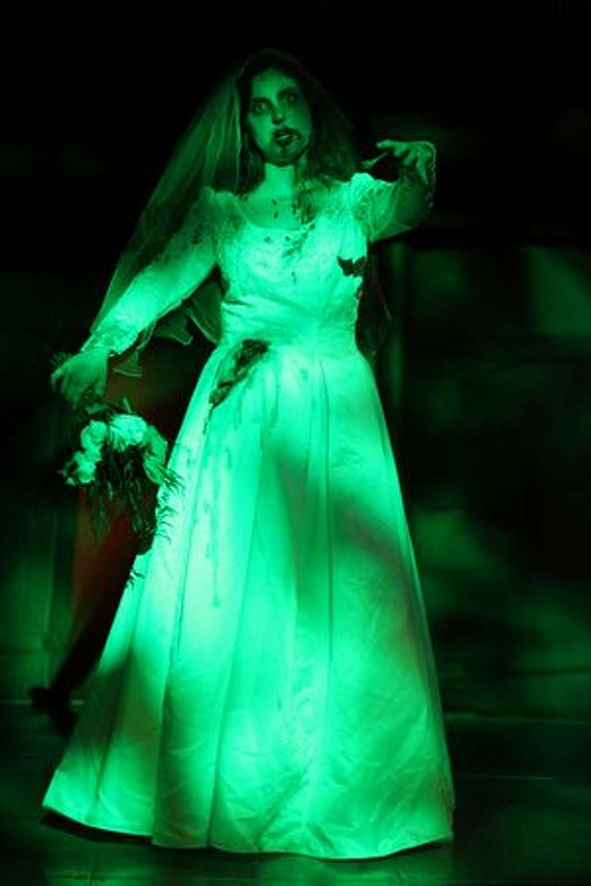 Bride Casey Russell of Seattle stands under a green spotlight during her zombie-themed wedding to Nathan Dooley on Saturday, October 30, 2010 at the EMP and Science Fiction Museum in Seattle. The wedding and a mass renewal of wedding vows after the legal ceremony were performed by actor Bruce Campbell as part of ZomBcon, a zombie convention. Campbell is known as a B-movie actor and star in a number of horror films.
