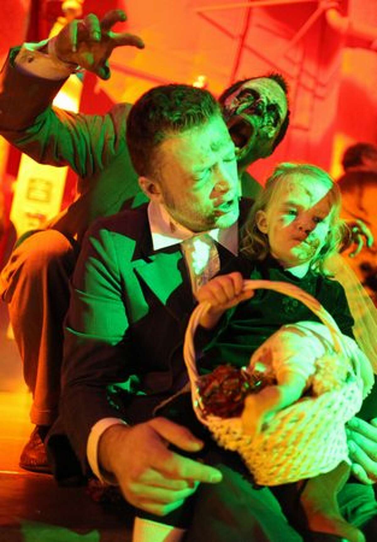 """Brian Byrne and flower girl Aya Byrne, 3, Brian's daugher, prepare to walk down the aisle as zombie Scott Grigg looms in the background. The """"zombies"""" were participating in a wedding ceremony as part of ZomBcon."""