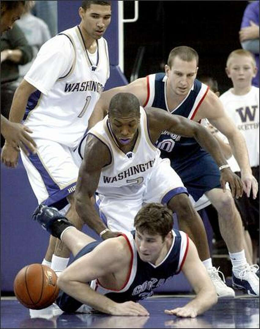 Washington's Nate Robinson and Gonzaga's Cory Violette, on floor, scramble for the ball in the first half.