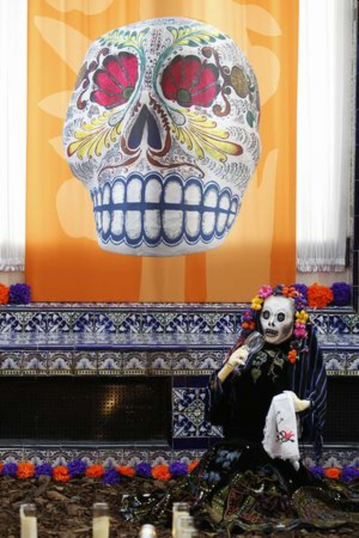 A statue of a skeleton sits near an altar assembled for a Day of the Dead exhibition at the Mexican Cultural Institute in Washington on Sunday in honor of the people who participated in the Mexican Revolution. (AP Photo/Jose Luis Magana)