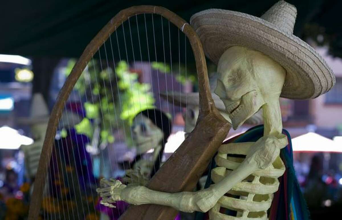 A skeleton as representation of the dead playing a harp in an Altar of the Dead at one of the parks in Mexico City on Sunday. Mexicans celebrate the Day of the Dead on November 1 and 2 in connection with the Catholic holy days of All Saints' Day and All Souls' Day. (OMAR TORRES/AFP/Getty Images)