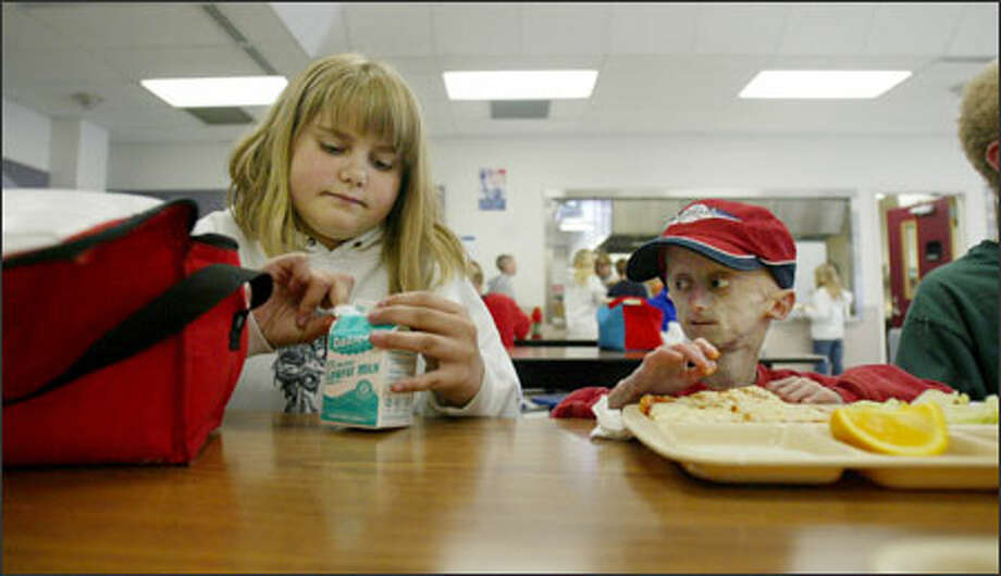 "Seth gets some help at lunch from his cousin Emily, whom he calls his ""can opener."" Arthritis in his fingers makes it difficult for Seth to open containers and packages, so he often relies on Emily, who eats at his table every day. Photo: Dan DeLong, Seattle Post-Intelligencer"