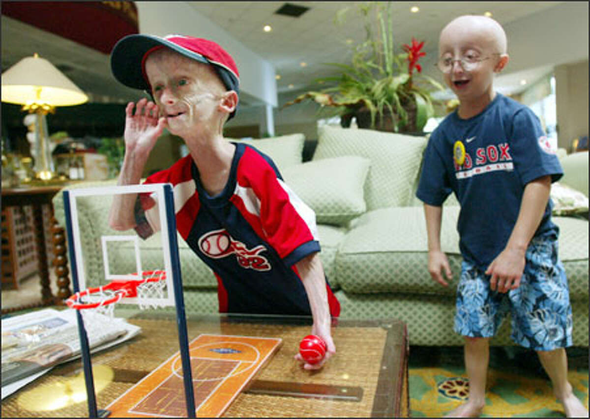 Seth gloats after defeating his father, Kyle, in a board basketball game during the Sunshine Foundation's annual progeria reunion in Orlando, Fla., in June. Sampson Berns, 7, of Foxboro, Mass., cheers him on. Sampson's parents, both doctors, are the founders of the Progeria Research Foundation, and were instrumental in finding the genetic mutation that causes progeria.