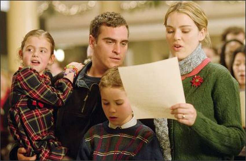 Linda (Jacinda Barrett, right) and Jack Morrison (Joaquin Phoenix, center left) share a tender moment with their children Katie (Brooke Hamlin, left) and Nicky (Spencer Berglund, center right) on Christmas Eve in Baltimore.