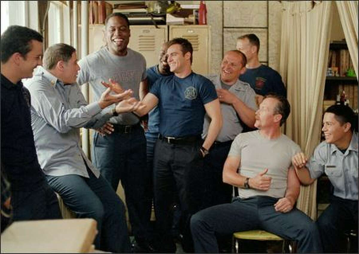 After pulling a prank on a rookie firefighter, Jack Morrison (Joaquin Phoenix, center) jokes with his comrades at the firehouse, including (Left to right) Ray Gauquin (Balthazar Getty), Captain Kennedy (John Travolta,), Don Miller (Kevin Daniels), Tommy Drake (Morris Chestnut), Frank McKinney (Kevin Chapman), Ed Reilly (Robert Lewis), Lenny Richter (Robert Patrick), and Keith Perez (Jay Hernandez).