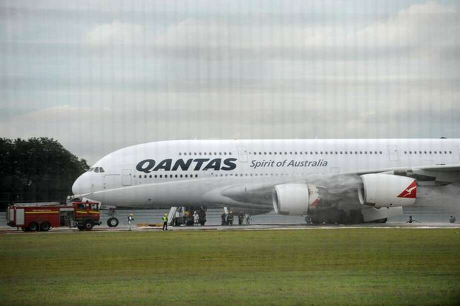 Fire services spray liquid at the engine of a Qantas Airbus A380 aircraft that was forced to make an emergency landing shortly after take-off, on the runway of Changi International airport in Singapore. Photo: Getty Images