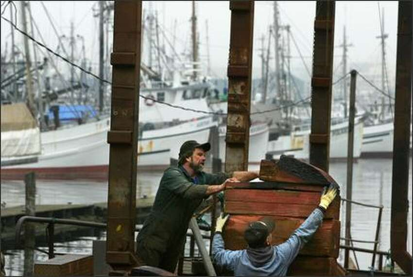 Beach gang crewmen Ernie Mezich (left) and Bill Corey prepare the haul out area to receive a boat at Fishing Vessel Owners Marine Ways, Inc. in Fishermen's Terminal. The shipyard, which was built in 1919 around the same time as Seattle's working fleet of halibut boats in the background, is slated for demolition to make way for construction of the monorail's green line.