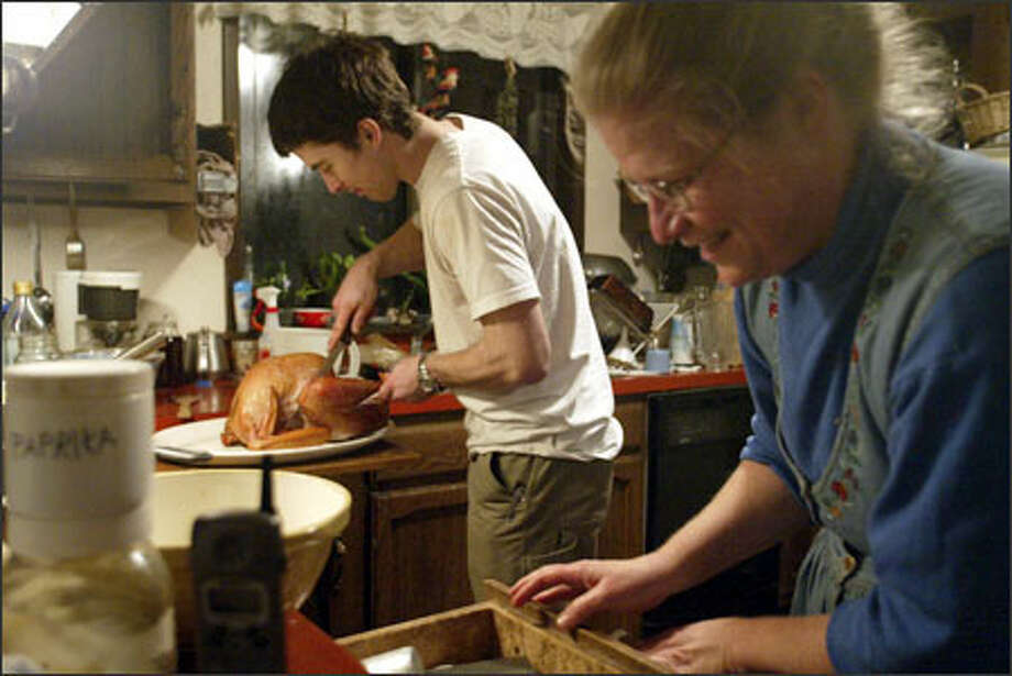 Eric Meier carves the smoked turkey as Deborah Dillon prepares for the pre-launch dinner. Meier and Storm eat at the Dillons' at least once a week. Photo: Mike Urban, Seattle Post-Intelligencer