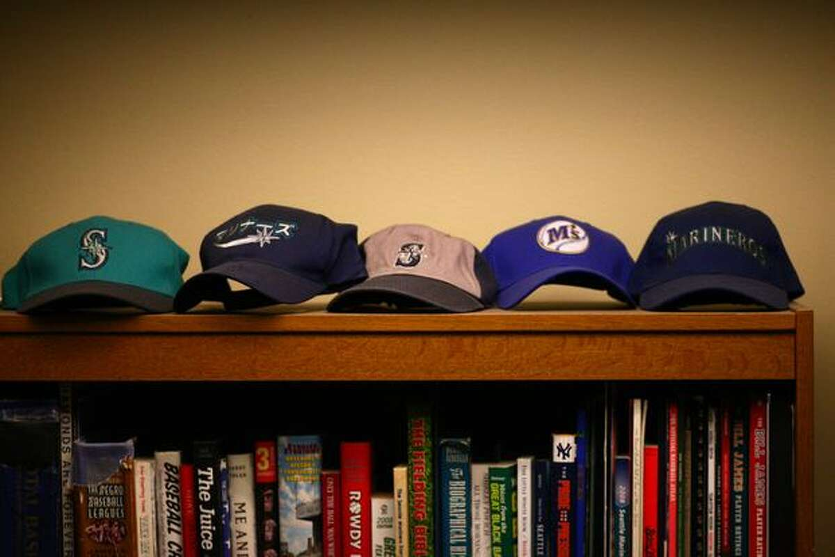 An assortment of Mariners baseball caps are shown inside the booth of Mariners broadcaster Dave Niehaus.