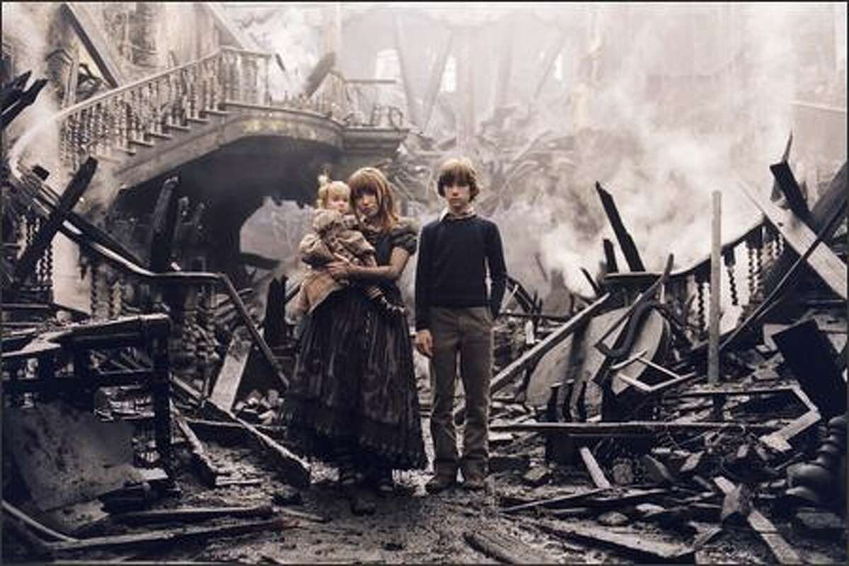 Sunny (played by Kara and Shelby Hoffman), Violet (Emily Browning) and Klaus (Liam Aiken) Beaudelaire are three talented children orphaned when their parents perish in a fire. Rest assured that any witticisms you may find in these captions are cribbed from the very amusing publicity materials.