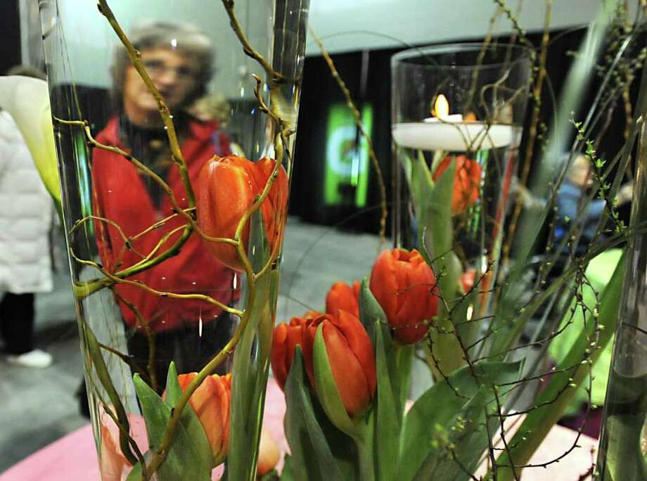 Adrienne Polenc looks at a dispay of flowers in water with flameless tea lights at the annual Capital District Garden & Flower Show at Hudson Valley Community College in Troy, NY on Friday, March 25, 2011. (Lori Van Buren / Times Union) Photo: Lori Van Buren