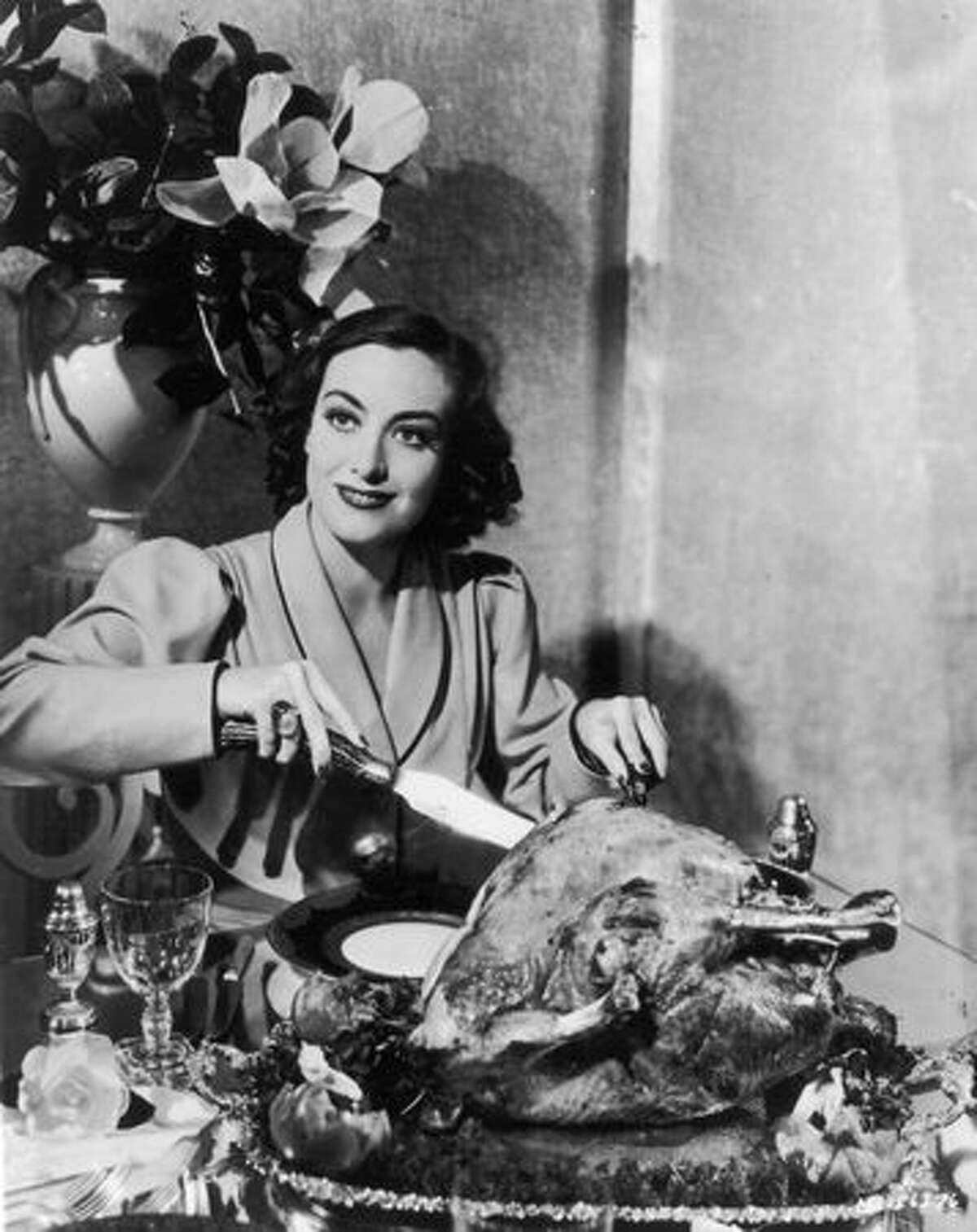 Circa 1930: American actress Joan Crawford (1908 - 1977) carves a huge Thanksgiving turkey for a publicity shot. Oddly, movie stars were often requested to strike this pose by their publicists.