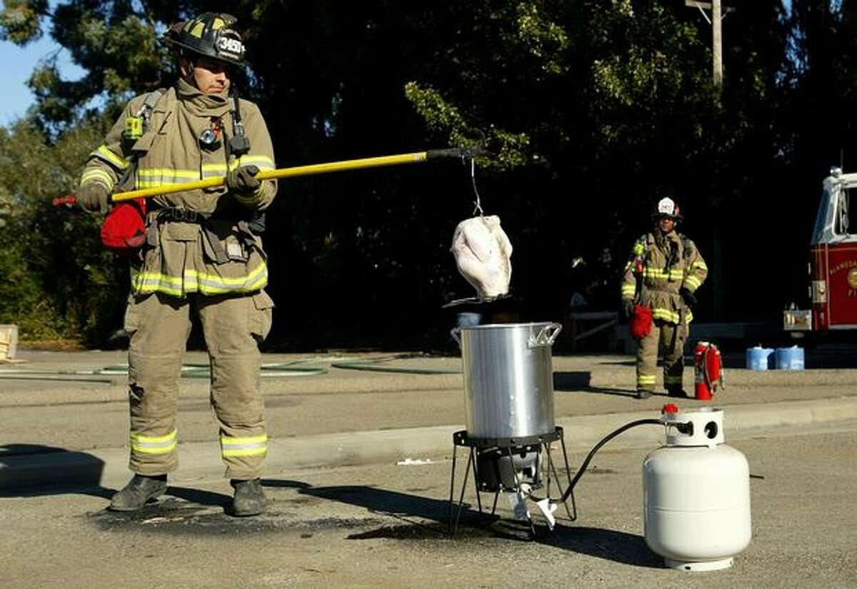 Click through the videos above to see what that looks like when it goes wrong, and have cooking guru Alton Brown explain how to do it right. Above, Alameda County firefighter Bob Perez prepares to lower a 13-pound turkey into a pot of boiling oil during a safety demonstration in San Leandro, Calif.