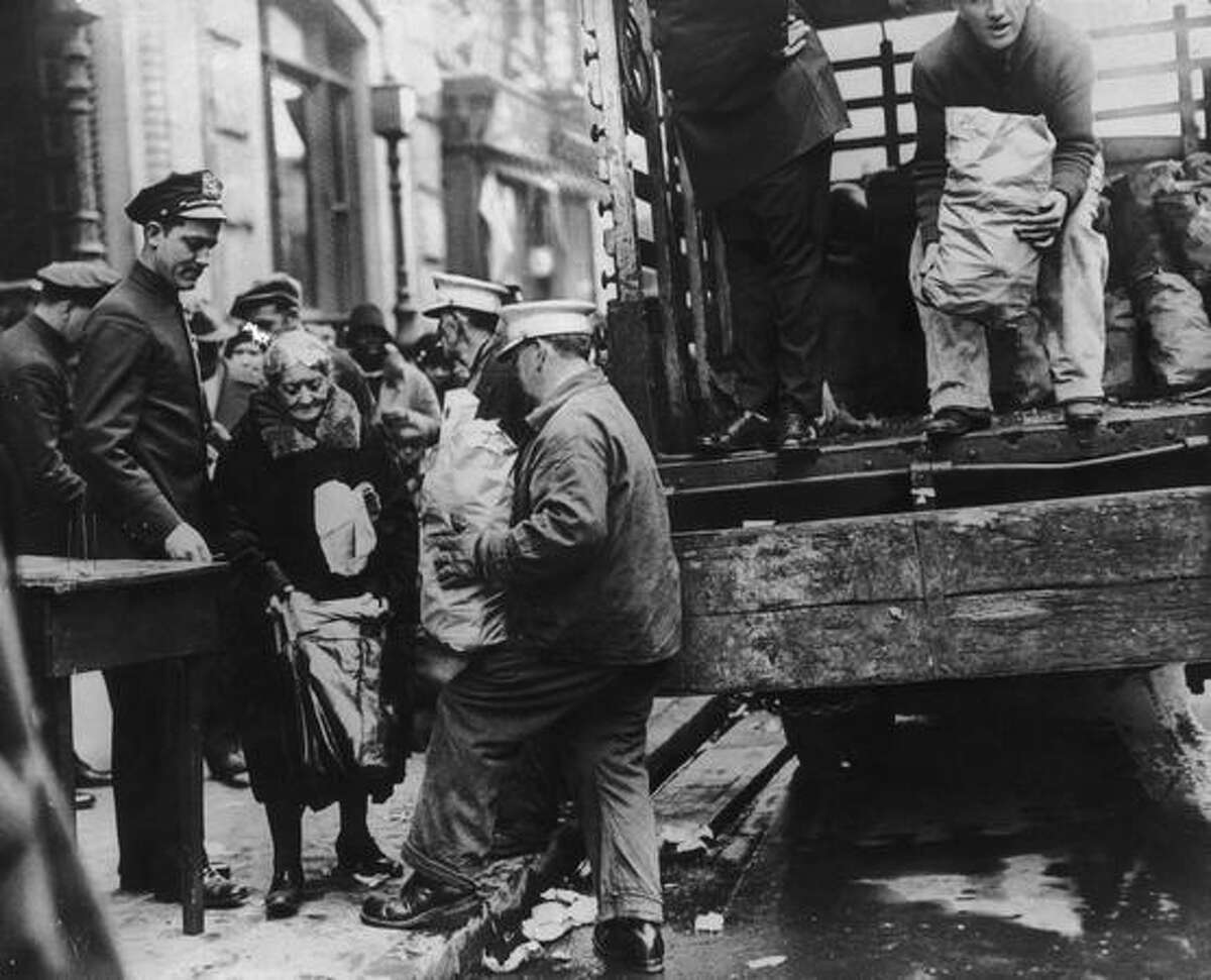 1930: An old woman receives her Thanksgiving ration of food in New York, during the Great Depression. Tons of food were distributed nationwide to the starving populace.