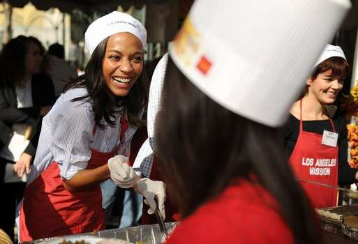 2009: Actress Zoe Saldana serves a Thanksgiving lunch for the homeless in downtown Los Angeles. Kirk Douglas and his wife Anne, namesake of the Anne Douglas Center for Women at the Los Angeles Mission, were hosts for this event, featuring the traditional Thanksgiving dinner. Photo: Getty Images