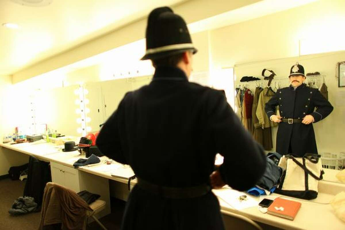 """Eric Riedmann, performing the role of Garrison, puts on his costume during a dress rehearsal for """"Sherlock Holmes and the Case of the Christmas Carol"""" at the Taproot Theatre in Seattle's Greenwood neighborhood."""