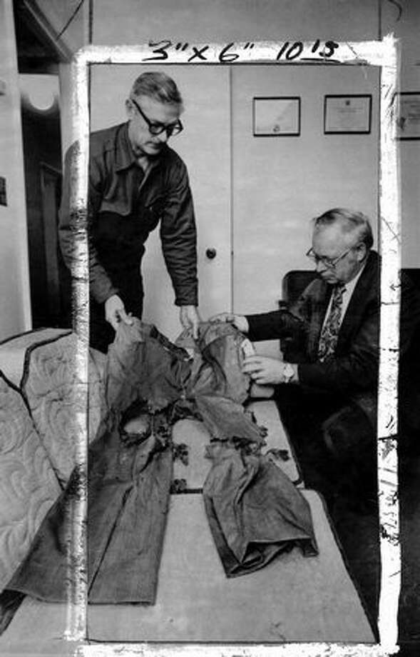 FBI Agent Dick Dyer of Vancouver, Wash., left, and Sheriff Gene Cotton of Clark County examine a pair of pants found in a tree about 25 feet off the ground in southwest Washington. The pants were thought to have belongd to D.B. Cooper, the only successful parachute skyjacker. The pants, photographed here Nov. 25, 1976, were not Cooper's. The hijacker has never been found.  (The Associated Press/provided by seattlepi.com file) Photo: P-I File