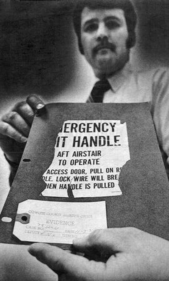 Jan. 17, 1979: Cowlitz County Sheriff's Detective Bob Nix displays an exit placard from a Boeing 727, found by a hunter the previous November near Toutle, Wash. The FBI confirmed the placard matched one missing from the plane hijacked by D.B. Cooper in November 1971.  (The Associated Press/provided by seattlepi.com file) Photo: P-I File