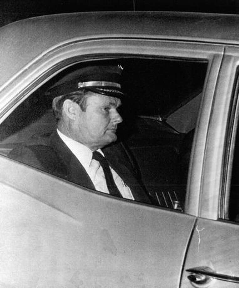 Northwestern Airlines pilot William Scott is whisked from the plane to a meeting with FBI agents after landing in Reno, Nev., November 1971.  (The Associated Press/provided by seattlepi.com file) Photo: P-I File
