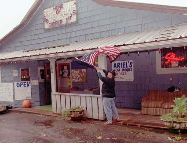 The 2001 photo caption read: Dona Elliott owner of the Ariel Store and Tavern puts up the flag getting ready for the annual D. B. Cooper party to be held Nov. 24th. (Phil H. Webber/seattlepi.com file) Photo: P-I File