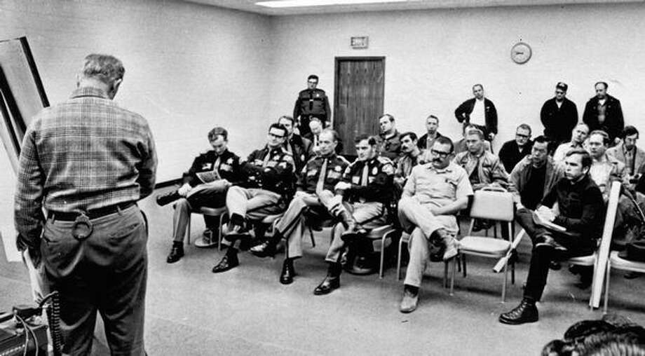 FBI Agent Tom Manning briefs officers at the command post in Woodlan City Hall, Nov. 26, 1971. FBI agents and sheirff's officers were instructed to look for the parachutes used by hijacked D.B. Cooper.  (The Associated Press/provided by seattlepi.com file) Photo: P-I File