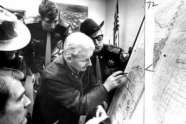 Nov. 26, 1971: FBI Agent Tom Manning, center, assigned search crews to sectors of area that authorities believed D.B. Cooper may have parachuted from the jetlilner. Gathered around the map at the Woodland command post are, from bottom left, helicopter pilot Bobby Hall, Sgt. M.A. Miller, Undersheriff Tom McDowell and Sgt. Arch Thornberry. (seattlepi.com file/Cary Tolman) Photo: P-I File