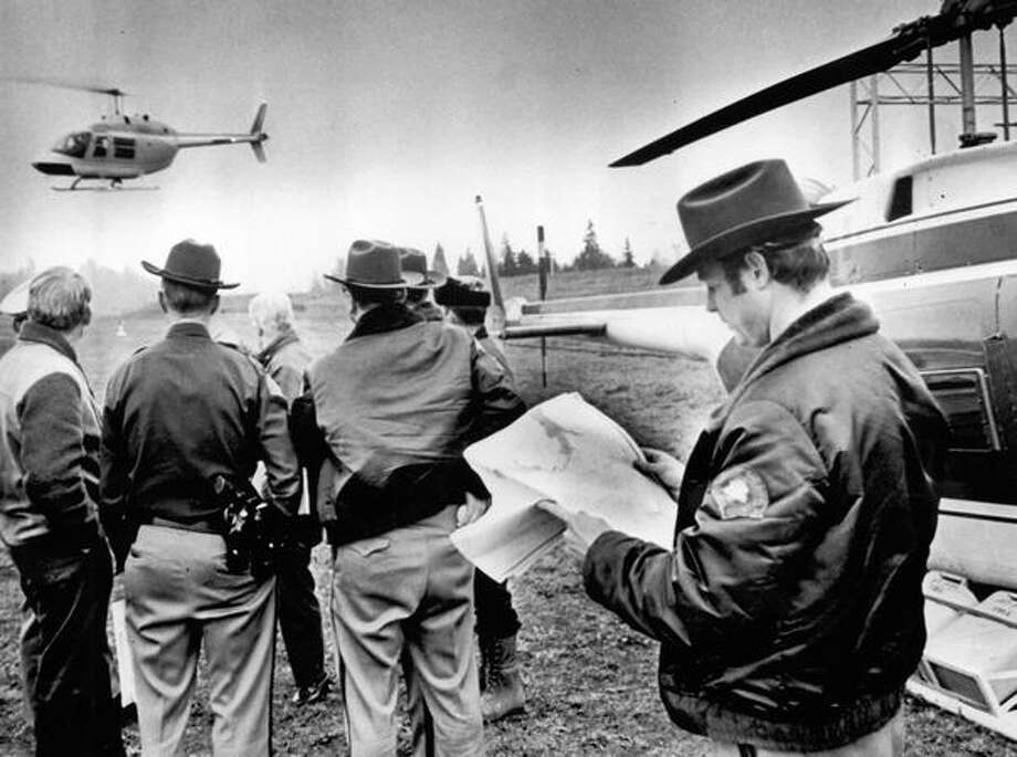 Nov. 26, 1971: A helicopter takes off from search headquarters as Clark County Deputy Sheriff Bob Rayburn checks a map of the area where D.B. Cooper parachuted from a hijacked Northwest Airlines flight.  (The Associated Press/provided by seattlepi.com file) Photo: P-I File