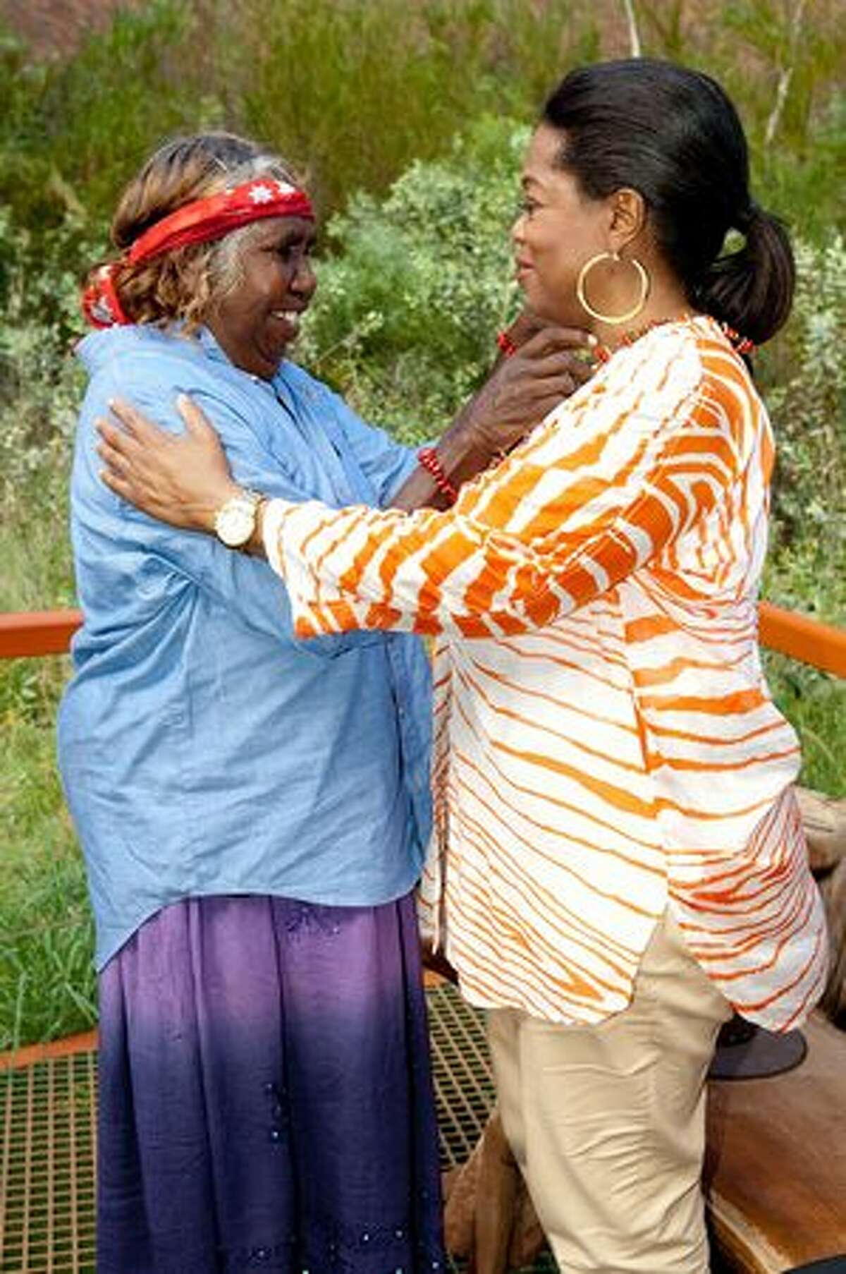 In this handout image provided by SDPmedia.com.au,TV personality Oprah Winfrey is presented with a necklace by Annangu Elder Judy Trigger at at Uluru on December 9, 2010 in Uluru, Australia. Oprah Winfrey is in Australia with 302 audience members from the US, Canada and Jamaica for the