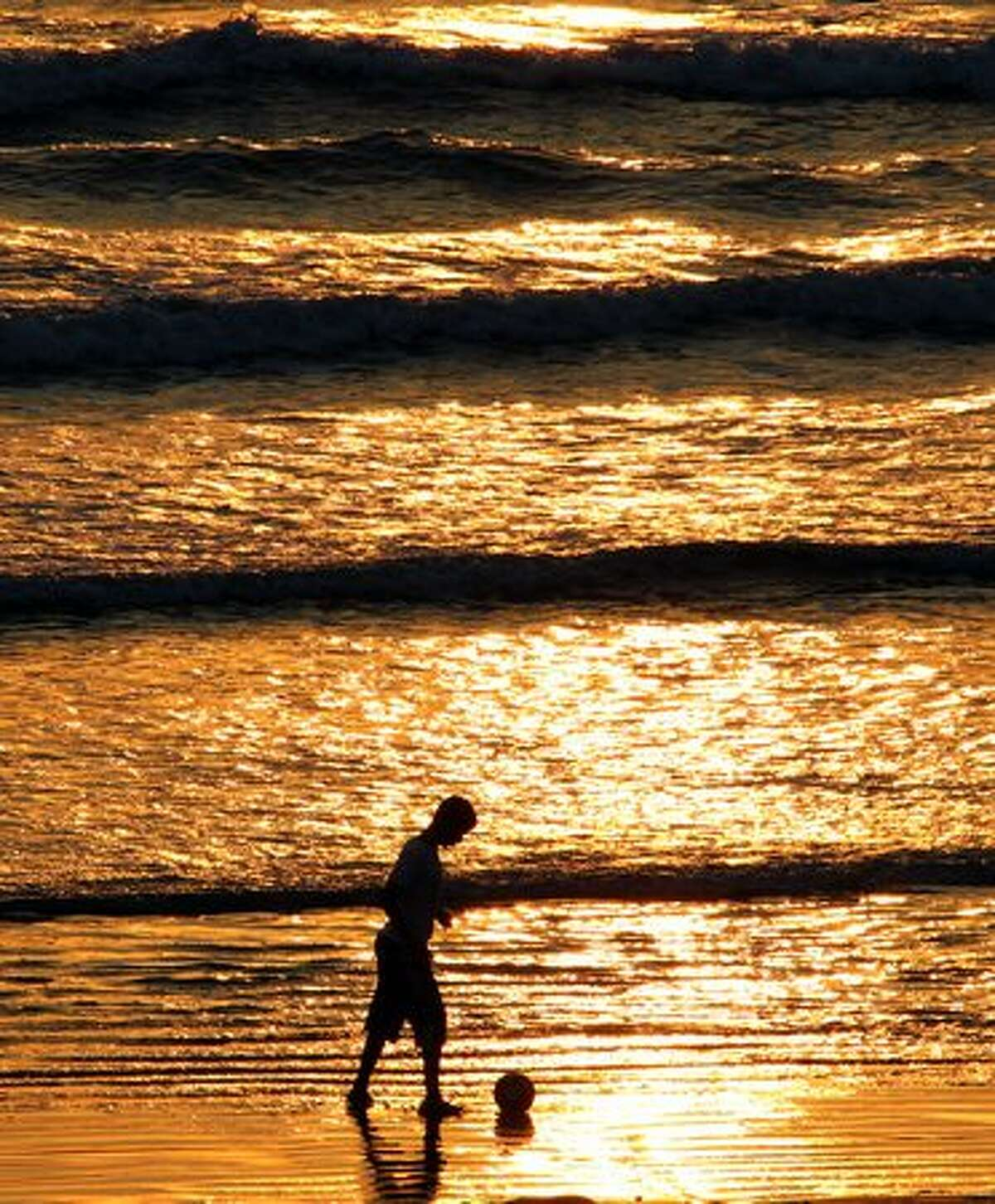 A Yemeni boy plays with a ball on the beach as the sun sets over the southern Yemeni city of Aden on December 3.