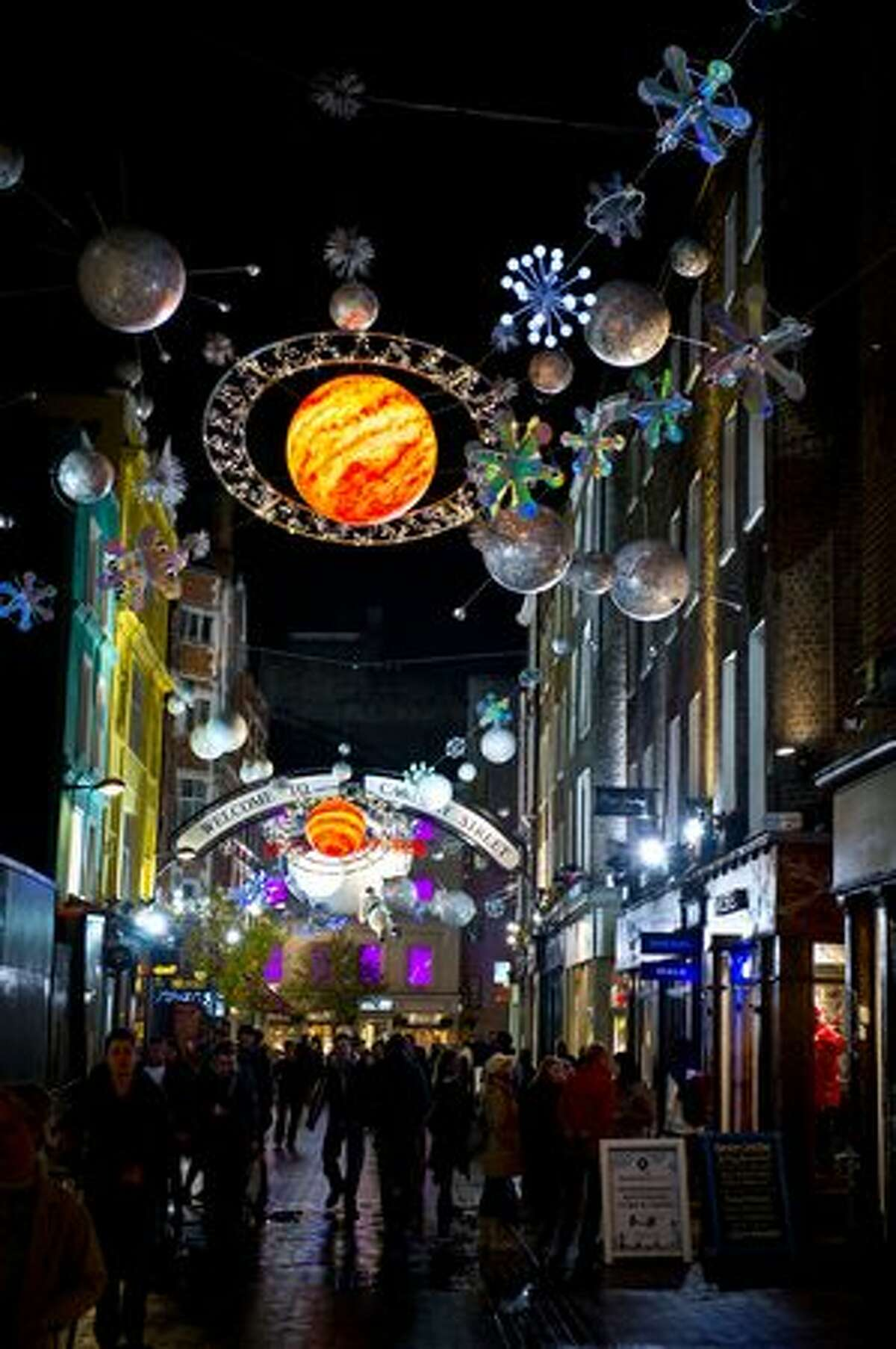 Pedestrians walk under the Christmas lights over Carnaby Street in London, England.