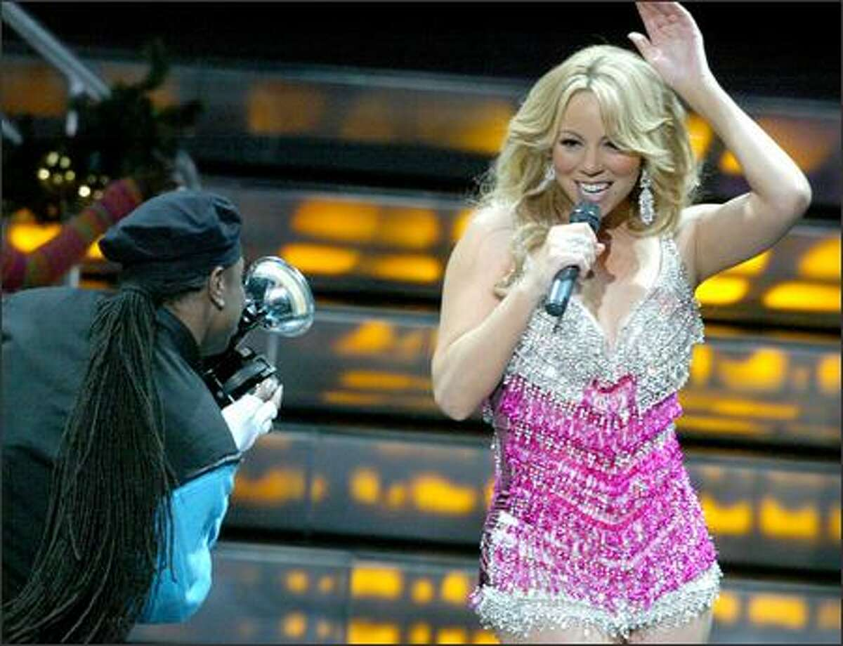Mariah Carey sings while a backup dancer photographs her. This was Carey's first concert in Seattle despite a career that has produced 15 No. 1 singles, two Grammy Awards and eight American Music Awards.
