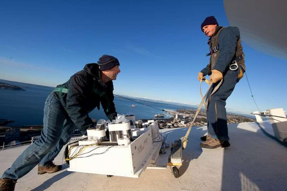 Scott Streeper, left, and Jon Berson install fireworks atop Seattle's landmark Space Needle in preparation for a New Year's show that will welcome in 2011. The crew started the installation early Thursday morning. Photo: Joshua Trujillo, Seattlepi.com
